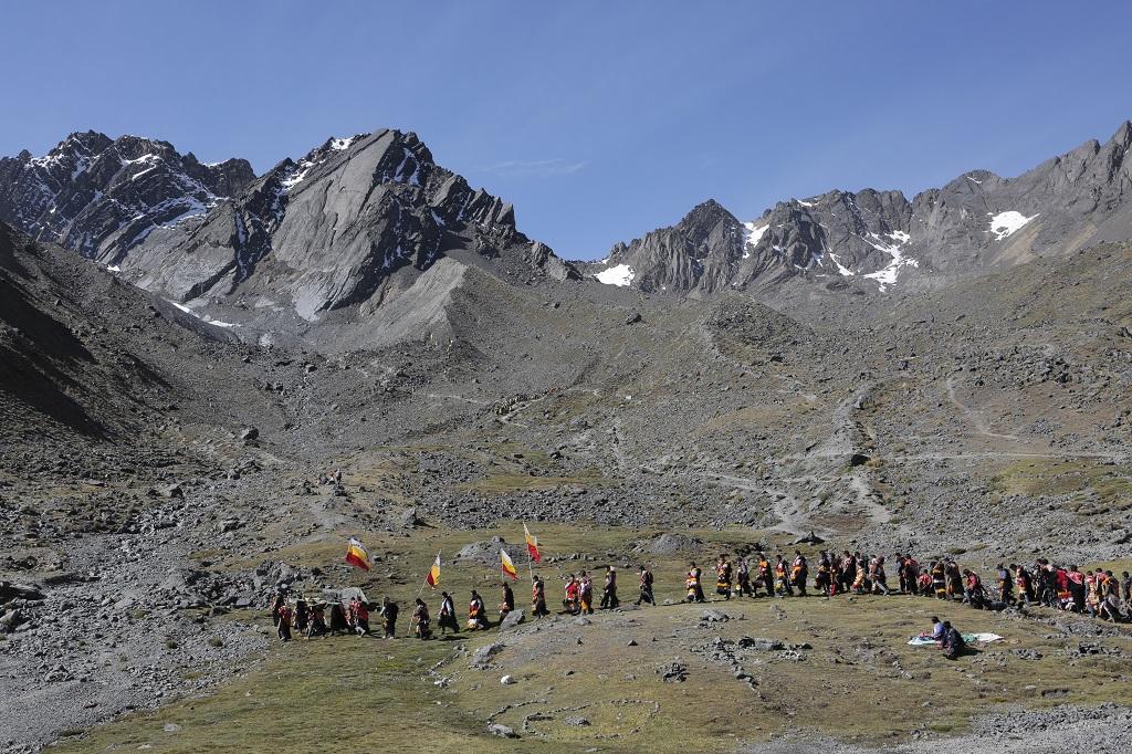 Au petit matin, les initiés, en transe, partent vers le glacier. La pente est très raide. Malgré l'altitude, beaucoup courent ou dansent à travers les éboulis en portant des croix ou de lourds étendards. - ©Alfred de Montesquiou