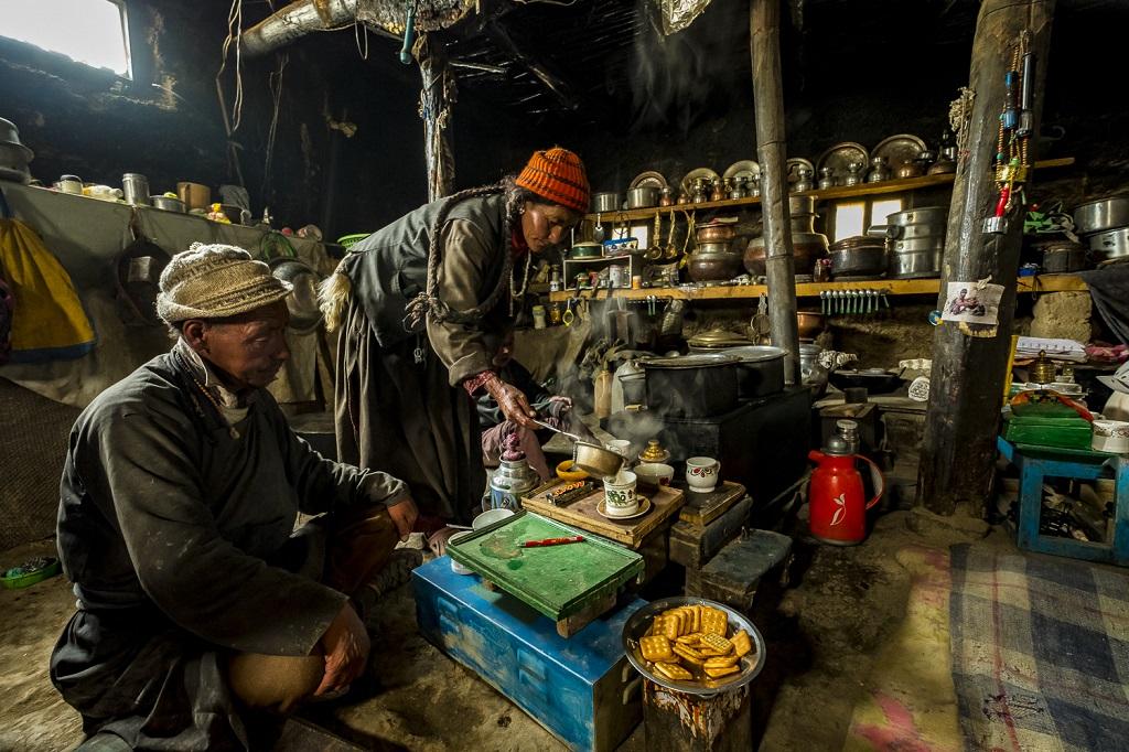 """Hospitalité toute ladakhie dans la demeure enfumée et """"dans son jus"""" de Siri Angchuk et son épouse Kunzes Dolma, en train de servir le thé au beurre salé à un photographe de passage"""